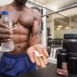 Shirtless muscular man holding vitamin pills — Stock Photo #50043349