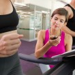 Trainer timing her client on the treadmill — Stock Photo #50043479