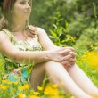 Cute young woman relaxing in field — Stock Photo #50043539