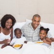 Happy family having breakfast in bed together in the morning — Stock Photo #50043837