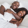 Happy couple cuddling together in bed — Stock Photo #50043887