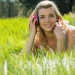 Pretty blonde lying on grass with headphones around neck — Stock Photo #50044045