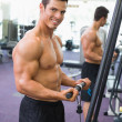 Shirtless muscular man using triceps pull down in gym — Stock Photo #50044125