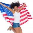 Pretty girl wrapped in american flag jumping — Stock Photo #50044181