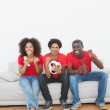 Football fans sitting on couch cheering together — Stock Photo