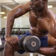 Muscular man exercising with dumbbell in gym — Stock Photo #50045141
