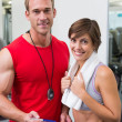 Handsome personal trainer with his client smiling at camera — Stock Photo #50045247