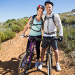 Active couple embracing on a bike ride in the country — Stock Photo
