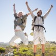 Couple on mountain terrain jumping — Foto de Stock