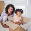 Cute daughter sitting in moving box with mother — Stock Photo #50045467