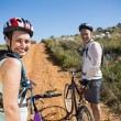 Active couple cycling on country terrain together — Stock Photo