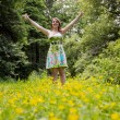 Woman with arms outstretched in field against trees — Stock Photo #50045901