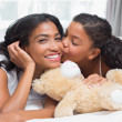 Pretty woman lying on bed with her daughter kissing cheek — Stock Photo #50046439