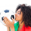 Pretty football fan with portugal flag kissing ball — Stock Photo #50046507