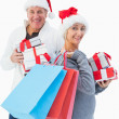 Festive mature couple in winter clothes holding gifts and bags — Stock Photo #50046549