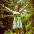 Woman with arms outstretched in field against trees — Stock Photo #50046585