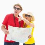 Happy tourist couple using map — Stock Photo