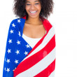 Pretty girl wrapped in american flag smiling at camera — Stock Photo #50047001