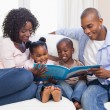 Happy family on the couch reading storybook — Stock Photo #50047057