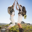 Couple on mountain terrain jumping — Stockfoto