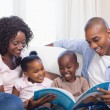 Happy family on the couch reading storybook — Stock Photo #50047133
