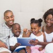 Happy family using tablet together on bed — Stock Photo #50047325