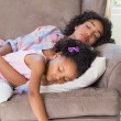 Pretty mother sleeping with her daughter on the couch — Stock Photo #50047641