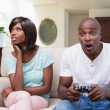 Woman sitting next to her boyfriend playing video games — Stock Photo #50048565
