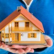 Hands holding miniature house model — Stock Photo #50048611