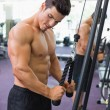 Shirtless muscular man using triceps pull down in gym — Stock Photo #50048677