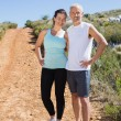 Fit smiling couple jogging down mountain trail — Stock Photo #50048873