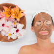 Smiling brunette getting a mud treatment facial beside bowl of f — Stock Photo #50049001