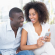 Attractive couple sitting on couch together looking at smartphon — Stock Photo #50049049