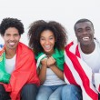 Football fans sitting on couch with flags — Stock Photo