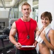 Handsome personal trainer with his client smiling at camera — Stock Photo #50049235