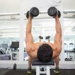 Muscular man exercising with dumbbells in gym — Stock Photo #50049283