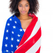 Pretty girl wrapped in american flag smiling at camera — Stock Photo #50049477