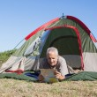 Happy camper looking at map lying in his tent — Stock Photo #50049485