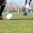 Football players tackling for the ball on pitch — Stock Photo #50049883
