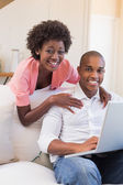 Cute couple relaxing on couch with laptop — Foto Stock
