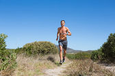 Shirtless man jogging with heart rate monitor around chest — Foto de Stock