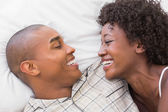 Happy couple lying in bed together — Stock Photo