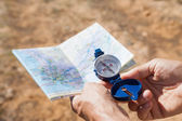 Hiker holding his compass and map in the countryside — Stock Photo