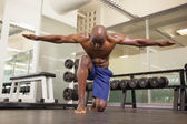 Bodybuilder with arms outstretched in gym — Foto de Stock
