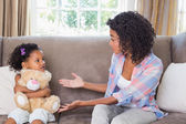 Pretty mother sitting on couch with petulant daughter — Stock fotografie