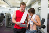 Handsome personal trainer with his client looking at clipboard — Foto Stock