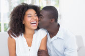 Attractive man kissing his girlfriend on the cheek — Stock Photo