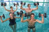 Happy fitness class doing aqua aerobics with foam dumbbells — Foto de Stock