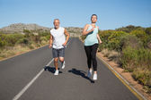 Fit couple running on the open road together — Stock Photo