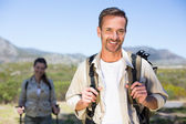 Hiking couple smiling at camera in the countryside — Foto Stock
